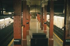 Bowery Northbound Platform - This view is from the stairs looking west down the south platform. The escalator would have dropped down just ahead where the three pairs of columns are closer together. In the distance is the stairway up to the closed west mezzanine. The wall at right is the dividing wall between the center tracks.