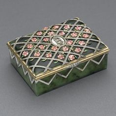 : A CARVED NEPHRITE, GOLD, ENAMEL AND JEWELED SNUFF BOX the hinged cover enameled with pink roses and green leaves on a diamond-set trellis extending down the sides, the center with the diamond-set imperial monogram Nicholas II of Russia, bearing imitation Cyrillic maker's mark of Fabergé and initials AH imitating mark of August Holllming Sotheby's, London, December 10, 1962, lot 107