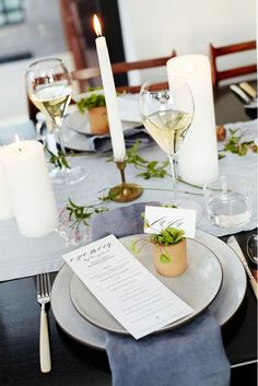 White candles and greenery pop against dark table linens