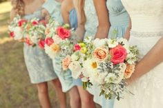 Bridesmaid dresses in various shades of light blue