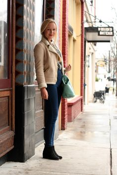 Anna Nordens is afirst-year from Norway studying Political Science and International Affairs at UGA. She is wearing a tan fur lined shearling jacket over a gray red and black print contrast collar shirt tucked into slim blue jean jeggings and black booties. She accessorized her look by putting her blond hair in a ponytail and carrying a mint green hand bag.