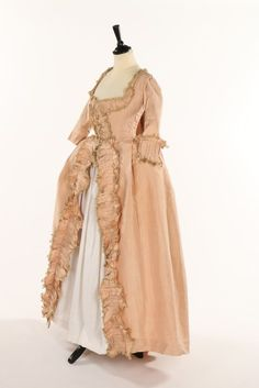 An old-rose silk robe à la Française, 1770s. the bodice with diagonal openings, the side slits, pleated silk cuffs and edges trimmed with pleated bands of matching silk edged in beige fly braid, and two panels of matching fabric, probably taken from the missing petticoat, one edged with fly braid