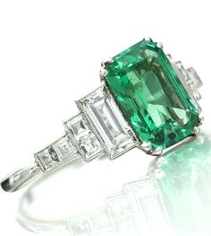 "A fine Art Deco emerald and diamond ring, circa 1926 Set with an octagonal-cut emerald to a double corner claw setting, the gallery pierced, between shoulders each set with a baguette-cut diamond and two pairs of square-cut diamonds, engraved inside the plain hoop ""A.M. 1926"" and stamped Pt, the emerald estimated to weigh approximately 1.70cts, size O"