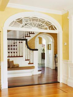 Trim with Curves     An ornate transom that was original to the house crowns the entry to the center hall, leading to an arched nook added during renovation. Choosing curvy designs adds softness to this home, balancing the room's heavier, more traditional wainscoting