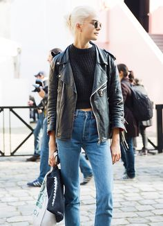 Black leather moto jacket, black knit sweater, and high-waisted jeans