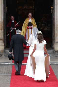 Catherine Middleton with the father Michael Middleton and Maid of Honour Pippa Middleton is greeted by The Very Reverend Dr John Hall (C), Dean of Westminster as they arrive to attend her Royal Wedding to Prince William at Westminster Abbey on April 29, 2011 in London, England.