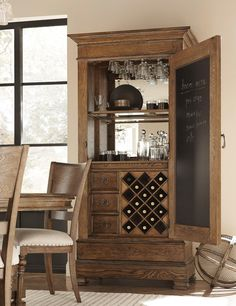 Impress your New Year's Eve party guests with a stylish Bohemian Vintner's Cabinet. Includes three full extension drawers and one large drawer with a working lock. A stemware holder is above two glass shelves in front of a mirrored back. Stores 18 bottles of wine and inside the door is a chalkboard.
