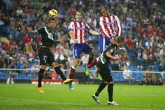 Atletico's Diego Gofin, top center, and Joao Miranda, top right, in action with Cordoba's Pinillos, left, during a Spanish La Liga soccer match between Atletico Madrid and Cordoba at the Vicente Calderon stadium in Madrid, Spain, Saturday, Nov. 1, 2014. (AP Photo/Andres Kudacki)