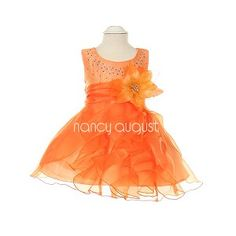 This Midnight Wave Sparkling orange dress features thin double straps with sprinkles of rhinestones crystal cascading down to accentuate the bodice. The natural waist is accented with a gorgeous detachable satin flower corsage. The tea length skirt is made with a sheer, crystal organza; a soft and gentle fabric that just flows! The light skirt is enhanced with multiple ruffles of sheer organza with an overlay wrap-around layer! Your beautiful princess will look elegant in this exquisite dres...