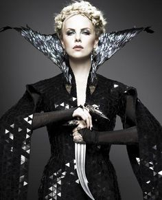 "Charlize Theron as the evil queen in ""Snow White and the Huntsman."" Love the way her dress has mirror bits, the feather collar, and her finger gauntlets."