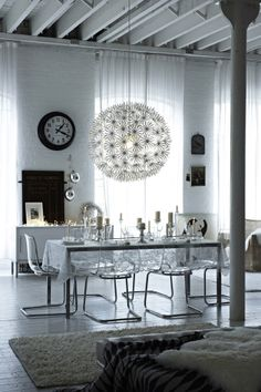 An icy cool glass-effect dining room with a snowball lampshade and a large white rug