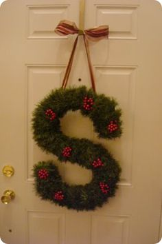Wrap wooden initial with garland & add lights, ornaments, berries etc then hang with ribbon on front door at Christmas :)
