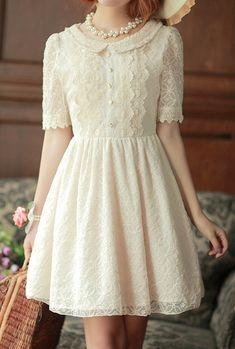 precioso vestido de encaje blanco de botones dorados y collar de perlas.