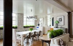 Love the white washed exposed brick walls. Charming long white dining table and the French metalcafe chairs