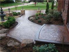 Beautifully stamped concrete entryway and driveway blend perfectly with surrounding landscape.