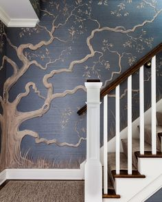 The foyer and main stairwell are high impact and timeless with a striking tree mural that reaches the home's second floor. Painted on a deep blue grasscloth, the tree's design was influenced by an oak tree in a nod to the client's Southern roots.