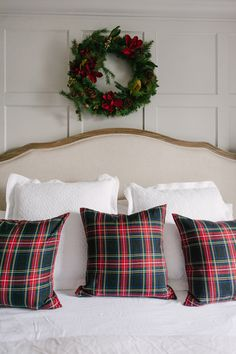 A bright red throw, plaid pillows and wreath give this #bedroom festive appeal