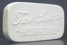 """Hopper Expositions Inc.'s Two Sisters Handmade Essentials Soap Bar Plaster Prototype. Rectangle shape, 4"""" x 2.25"""" x 0.875"""" thick, rounded corners, slight rounded surface edge, raised Company logo/artwork lettering on surface of soap bar. Company located in Ohio, USA. www.hopperexpos.com . Facebook Page: Two Sisters Handmade Essentials"""