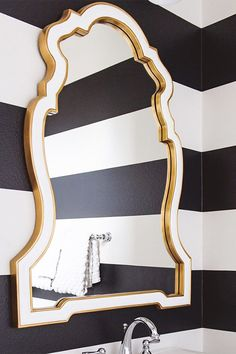 The Howard Elliott Cleopatra Mirror is shown here in a bathroom designed by Inside by Savvy Interior Design. The Mirror is fashioned with an Art Deco flair. The main frame is shaped like a fancy key hole. It is then finished in a lovely glossy white lacquer, then trimmed on the inner and outer borders in a gorgeous gold leaf. #bathroommirror #fancymirror #howardelliottmirror