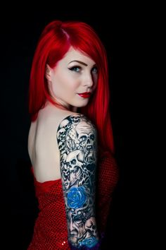 Woman with red hair and full sleeve ink work. Love the blues against the red-orange hair & dress.