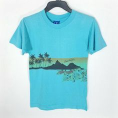 Vintage 1980s surfer on tropical ocean waves printed short-sleeved t-shirt. - Brand: Ocean Pacific, made in U.S.A - Size: X-large. Best fits mens sz small. Measurements laid flat:  Shoulder span 17  Bust 21  Waist 20  Length 27 - Color: Light blue with various color print - Fabric: 100% cotton - Very good condition; Average wear from laundry. No stains, rips, or other flaws. **Please send a message through Etsy with any questions. **Combined/reduced shipping for multiple store purchases...
