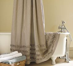 "Pottery Barn Ticking Stripe Ruffled Shower Curtain and ""claw"" foot tub. Yay for ticking!"