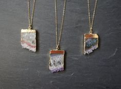 "{2016 --- prefer the ones without brown, 24"" link chain} Amethyst Stalactite pendant edged in gold on a custom length gold filled chain, select from two chain designs: link or satellite. Each slice is unique and beautiful with shards of Amethyst crystal or Druzy crystal formations. Select from your pendant from the available options. Your one-of-a-kind necklace will arrive in a gift box and on a hang tag noting the metaphysical properties of the crystal.  Stone: sliced & polished Amethyst…"