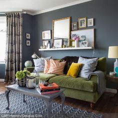 Die grau-blaue Wand verleiht dem Wohnzimmer Charakter. Das gemütliche Stoffsofa in Grün und die Bilderrahmen darüber machen den Raum schön wohnlich. Der Teppich…