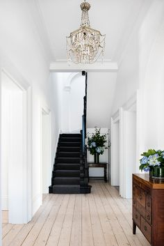 Natural wood floors mixed with white walls and black staircase in this Historic Australian Home Renovation by SJB