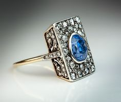 An Unusual Antique Sapphire and Diamond Engagement Ring circa 1900 The rectangular silver topped 18K gold ring is centered with an egg-shaped faceted natur