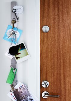 A magnet strip with keys and notes attached and fixed next to the door
