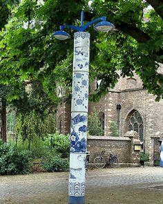 """Op het plein van Museum Het Prinsenhof zijn  de lantaarnpalen omkleed met """"Delfts Blauw""""."""