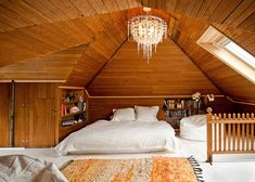 attic bedroom, natural light, chandelier, wood + white