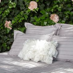 Pleated gray bedding, with a white ruffled pillow