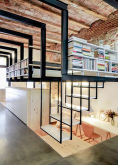 Three different levels of living space fit within what used to be a dilapidated basement laundry room in Barcelona, the floor excavated to create a study and nursery. You can either step down into this timber-lined subterranean space, or up into a combination bookcase, staircase and loft, with black I-beams and new white walls set against the original brick.