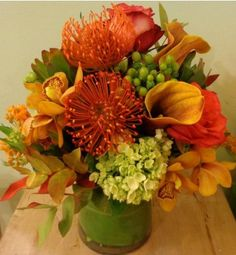 Pincushion Protea, Mango Calla Lilies, Mini Cymbidium Orchids and other seasonal flowers designed in a clear glass vase with foliage wrap inside. Perfect for every occasion.