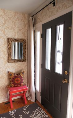 such a fresh idea instead of shears shirred on poles ... drapes hanging at the front door. What a great solution, these drapes with their trim detail running down the edge, for a door that doesnt offer any privacy at night with its multiple windows