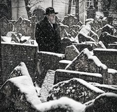A man explores the souls of the lost at a Jewish cemetery in snow