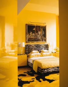 #master #bedroom, bright yellow provides the surprise element – the color. Here, the zebra-striped, upholstered bed and a moody painting of death masks add an element of fantasy. #interiordesign