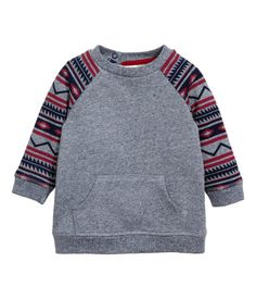 Dark blue melange. Soft sweatshirt with long, patterned raglan sleeves, kangaroo pocket at front, and snap fasteners at back.