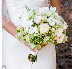 Bridal bouquet arrangement of roses, lilies, hydrangeas, and hypericum berries mixed with other greenery to complement her gown. #green #wedding inspiration