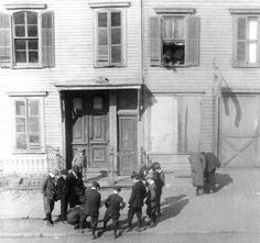 Boys in knickers, suits, caps and ties shoot marbles on the sidewalk while two young rascals look on from a window in a 1800s wood frame house. 41 Sumpter Street in Williamsburg. Brooklyn, New York.  1915 by wavz13, via Flickr