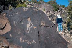 Archaeologist Janet MacKenzie, right, looks over some of the petroglyphs on basalt rocks along the Mesa Prieta. (Eddie Moore/Albuquerque Journal)