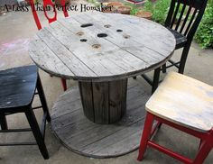 Sand - maybe paint and add an umbrella.  Use smaller cable spools to create seating - add foam and cover with fabric or use an old wooden palette for seating.