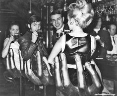 Young adults enjoying drinks at a high kitsch 'funfair house' in Munich, 1969.