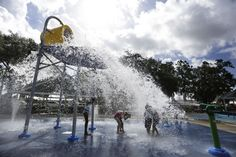 Children play in the splash pad at the 5-acre Water Works Park on opening day, Tuesday. The centerpiece of the splash pad is a big yellow water bucket that tips over about every two minutes to soak everyone below.