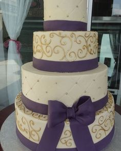 wedding+cake+with+gold+accents | Layered cake with gold accents, purple ribbon work