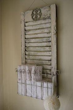 Oud luik/shutter met zelfgemaakt mandje van stukje gaas (de uiteinden zijn kromgebogen).