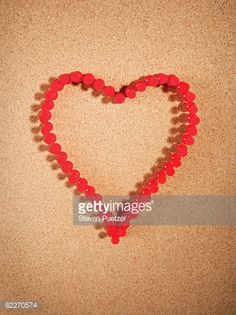 Stock Photo : Red push pins on corkboard in the shape of a heart