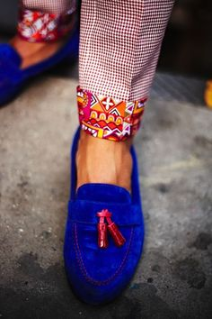 Pants w/colorful print cuffs and royal blue suede shoes w/red tassel.